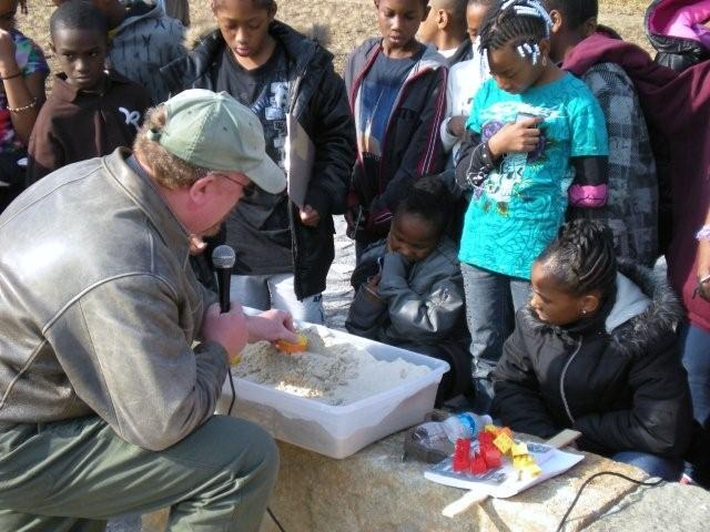 Fourth grade students from Swansboro Elementary School learn from Selden Richardson how archaeological sites get buried.