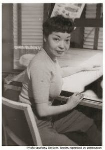 Jackie Ormes sitting at a drafting table looking at the camera