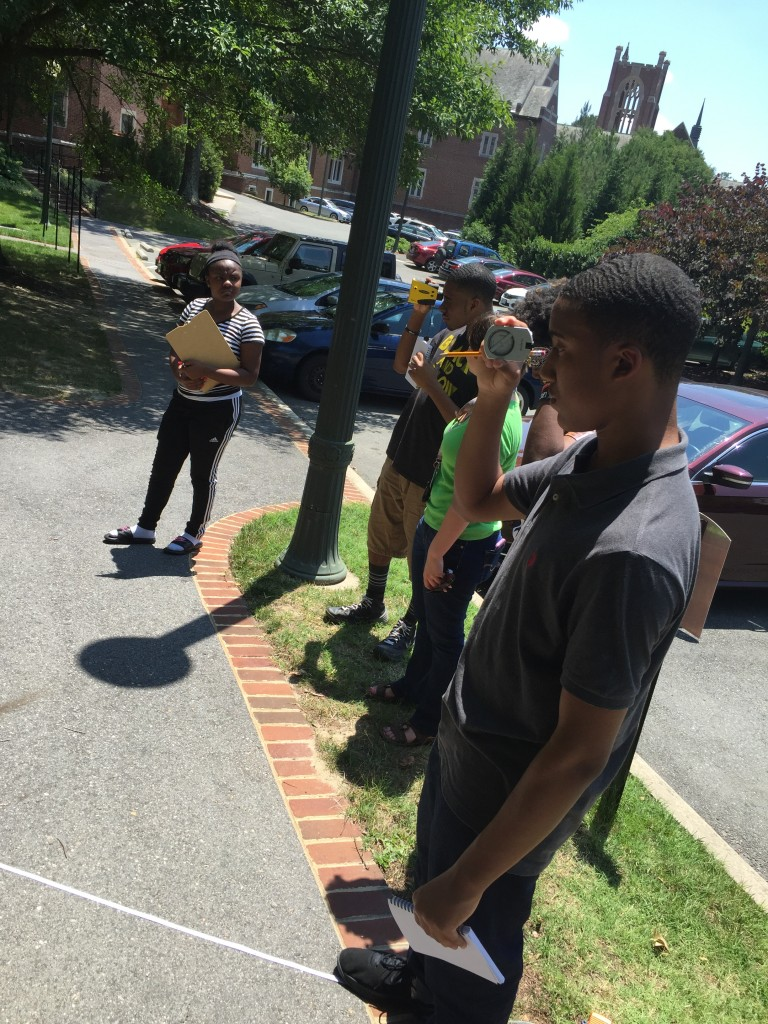 Students using the laser range finder, after having measured their distance from the tree using the tape measure on the ground.