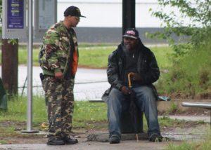 Dos viajeros buscan refugio de la lluvia mientras esperan el autobús. Foto por Brooke Warner