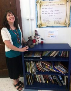 Elaine Hinkle stands next to the books and toys the center has for children. They all are free to take home. Photo by Thess Pfferr